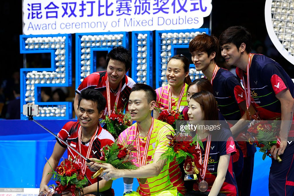 Gold medalists Zhao Yunlei (C) and Zhang Nan of China use a selfie stick to take photos with silver medalists Tontowi Ahmad ( L) and Liliyana Natsir of India and bronze medalists Ko Sung Hyun (R) and Kim Ha Na of South Korea and Shin Baek Cheol and Chae Yoo Jung of South Korea pose after the award ceremony of the mixed doubles at the 2016 Badminton Asia Championships in Wuhan, central China's Hubei province on May 1, 2016. / AFP / STR / China OUT