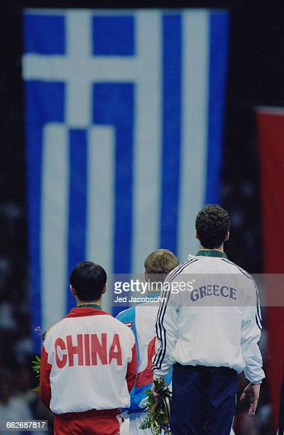 Gold medallist and Olympic champion Ioannis Melissanidis of Greece stands beside Li Xiaoshuang of China and Aleksey Nemov of Russia at the...