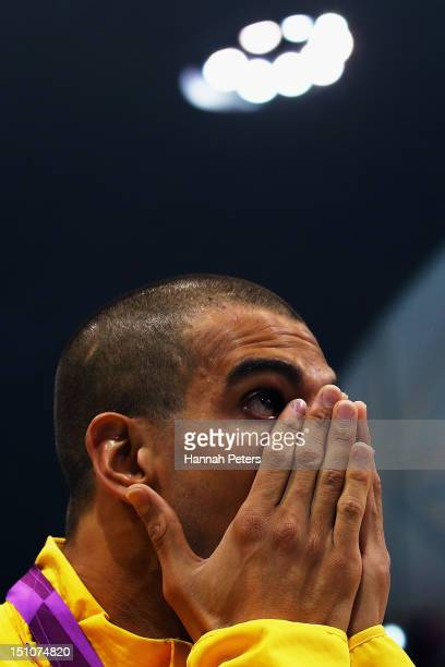Gold medallist Andre Brasil of Brazil wipes tears away after receiving his medal during the medal ceremony for the Men's 50m Freestyle S10 Final on...