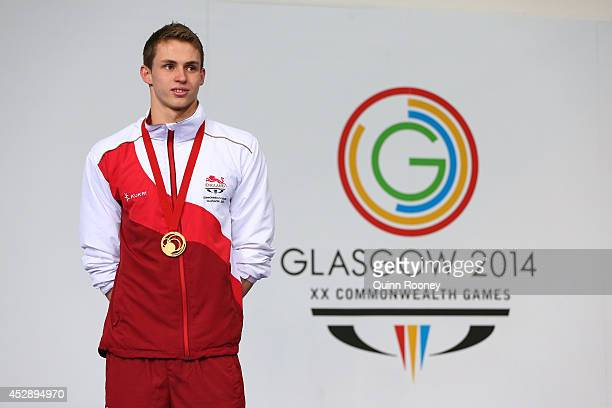 Gold medallist Benjamin Proud of England stands on the podium during the medal ceremony for the Men's 50m Freestyle Final at Tollcross International...