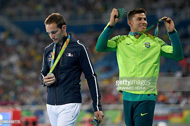 TOPSHOT Gold medallist Brazil's Thiago Braz Da Silva and silver medallist France's Renaud Lavillenie attend the medal ceremony for the men's pole...