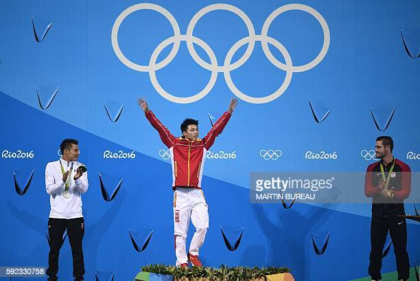 Gold medallist China's Chen Aisen celebrates next to silver medallist Mexico's German Saul Sanchez Sanchez and bronze medallist USA's David Boudia...