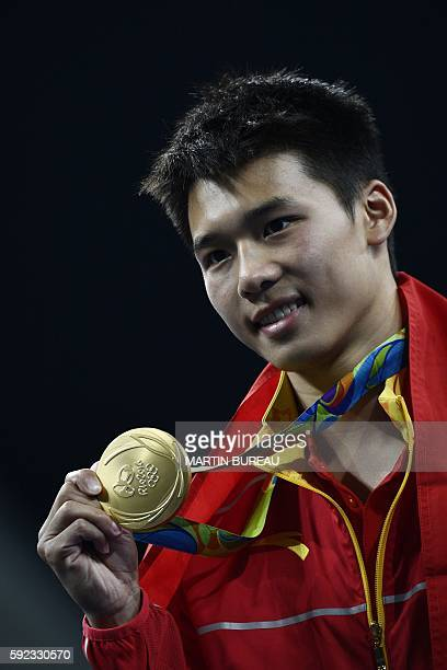Gold medallist China's Chen Aisen poses during the podium ceremony of the Men's 10m Platform final during the diving event at the Rio 2016 Olympic...