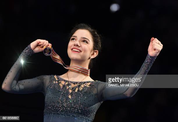 TOPSHOT Gold medallist Evgenia Medvedeva of Russia celebrates with her medal on the podium after the woman's Free Skating event at the ISU World...