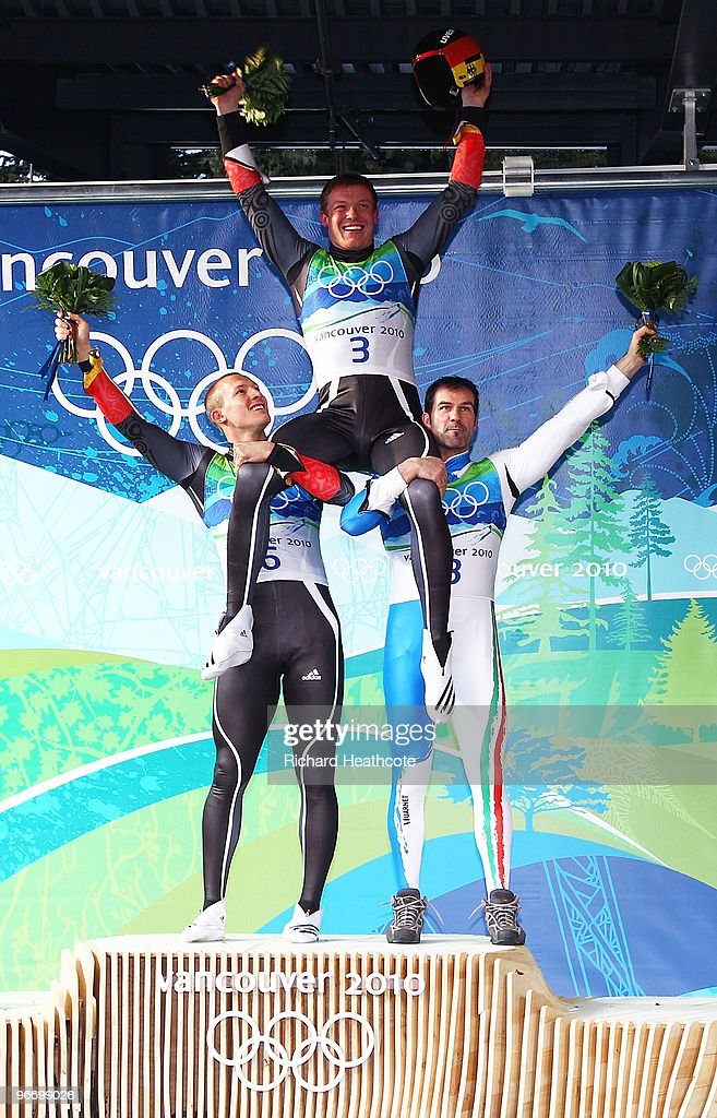 Gold medallist <a gi-track='captionPersonalityLinkClicked' href=/galleries/search?phrase=Felix+Loch&family=editorial&specificpeople=4840944 ng-click='$event.stopPropagation()'>Felix Loch</a> of Germany is held aloft by silver medallist <a gi-track='captionPersonalityLinkClicked' href=/galleries/search?phrase=David+Moeller&family=editorial&specificpeople=791406 ng-click='$event.stopPropagation()'>David Moeller</a> of Germany (R) and bronze medallist <a gi-track='captionPersonalityLinkClicked' href=/galleries/search?phrase=Armin+Zoeggeler&family=editorial&specificpeople=227382 ng-click='$event.stopPropagation()'>Armin Zoeggeler</a> of Italy after the final run of the men's luge singles final on day 3 of the 2010 Winter Olympics at Whistler Sliding Centre on February 14, 2010 in Whistler, Canada.