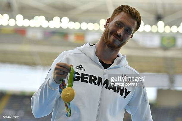 Gold medallist Germany's Christoph Harting celebrates on the podium for Men's Discus Throw athletics event at the Rio 2016 Olympic Games at the...