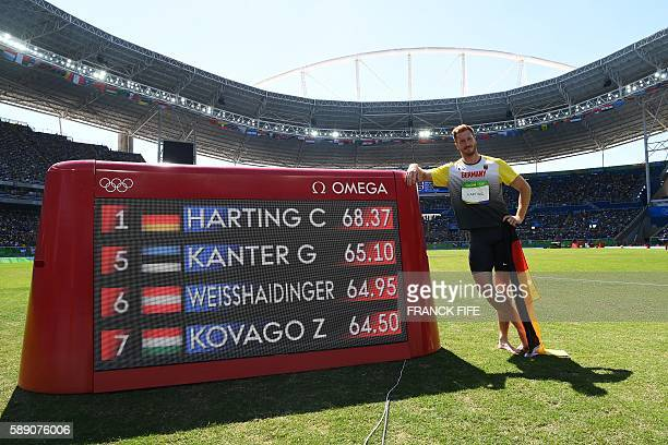 Gold medallist Germany's Christoph Harting poses next to a board displaying his throw after winning the Men's Discus Throw Final during the athletics...