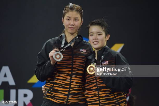 Gold medallist Goh Jin Wei and silver medallist Soniia Cheah of Malaysia pose with their medals after the women's singles badminton final at the 29th...
