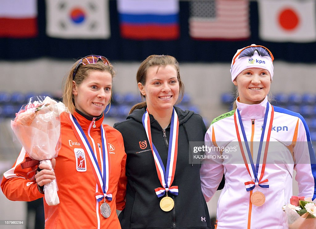 Gold medallist Heather Richardson of the US (C), silver medallist Christine Nesbitt of Canada (L) and Lotte van Beek of the Netherlands (R) celebrate on the podium during the awards ceremony for the women's 1,000 meters competition at the World Cup speed skating event at the Nagano M-Wave ice arena on December 8, 2012. Richardson clocked the fastest time of 1:15.24 seconds in the event. AFP PHOTO / KAZUHIRO NOGI