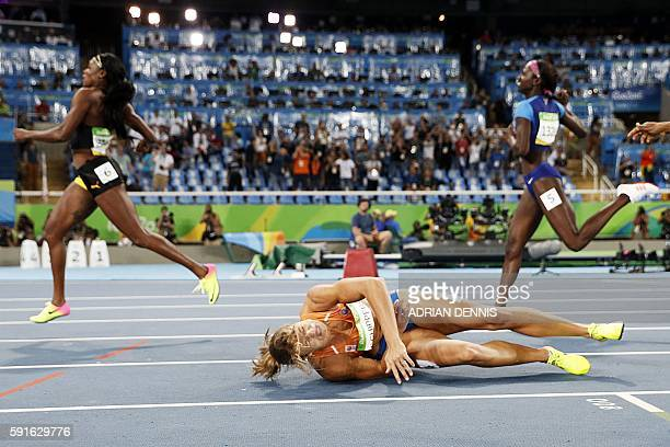 TOPSHOT Gold medallist Jamaica's Elaine Thompson runs as silver medallist Netherlands' Dafne Schippers falls after crossing the finish line ahead of...