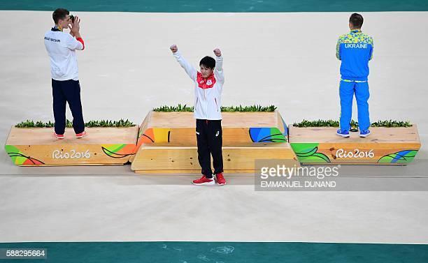 Gold medallist Japan's Kohei Uchimura celebrates next to silver medallist Ukraine's Oleg Verniaiev and bronze medallist Britain's Max Whitlock on the...