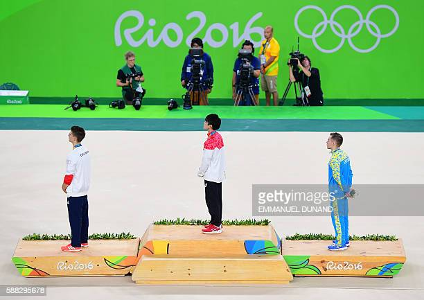 Gold medallist Japan's Kohei Uchimura silver medallist Ukraine's Oleg Verniaiev and bronze medallist Britain's Max Whitlock listen to the Japanese...