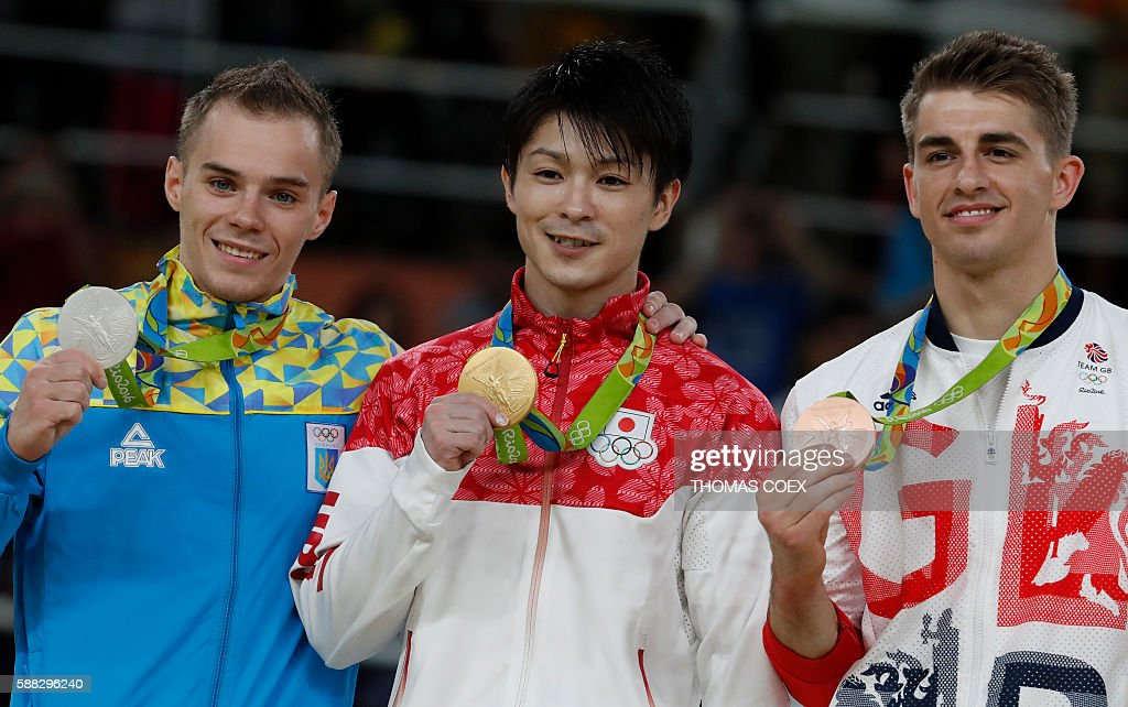 Gold medallist Japan's Kohei Uchimura (C), silver medallist Ukraine's Oleg Verniaiev (L) and bronze medallist Britain's Max Whitlock pose on the podium of the men's individual all-around final of the Artistic Gymnastics at the Olympic Arena during the Rio 2016 Olympic Games in Rio de Janeiro on August 10, 2016. / AFP / Thomas COEX