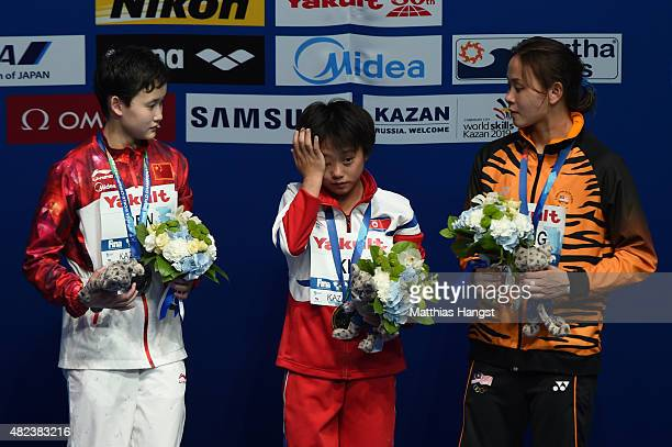 Gold medallist Kuk Hyang Kim of Democratic People's Republic of Korea wipes away tears with silver medallist Qian Ren of China and bronze medallist...