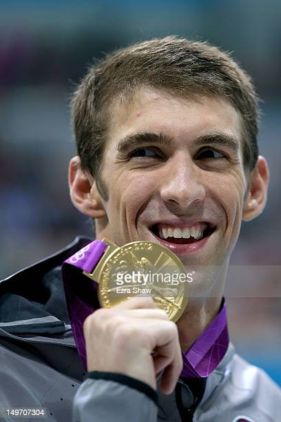 Gold medallist Michael Phelps of the United States poses with the medal won in the Men's 200m Individual Medley final on Day 6 of the London 2012...