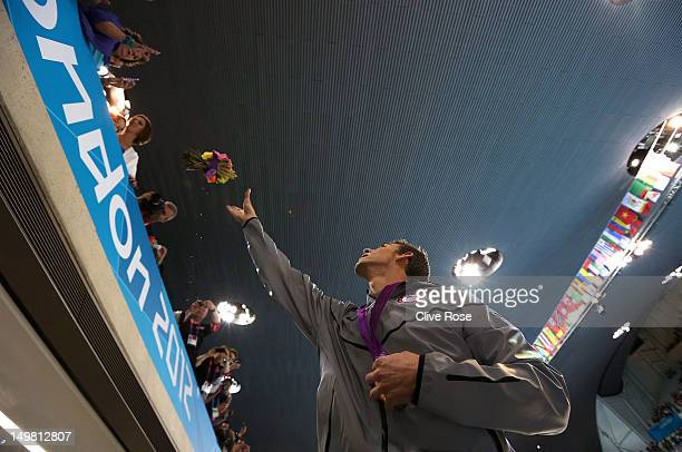 Gold medallist Michael Phelps of the United States throws his ceremonial flowers to his mother Debbie Phelps following the medal ceremony for the...
