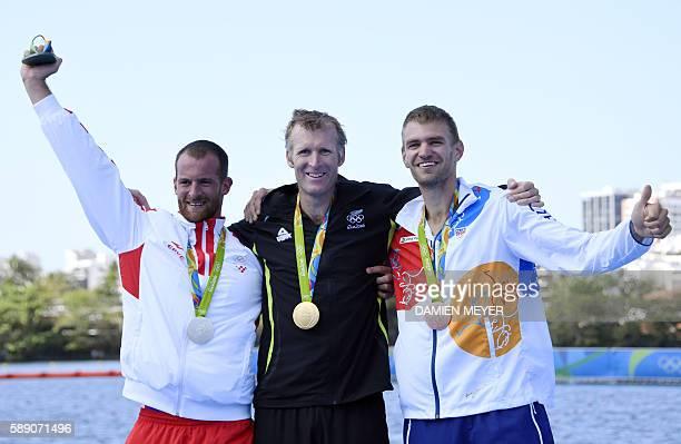 Gold medallist New Zealand's Mahe Drysdale is flanked by silver medallist Croatia's Damir Martin and bronze medallist Czech Republic's Ondrej Synek...