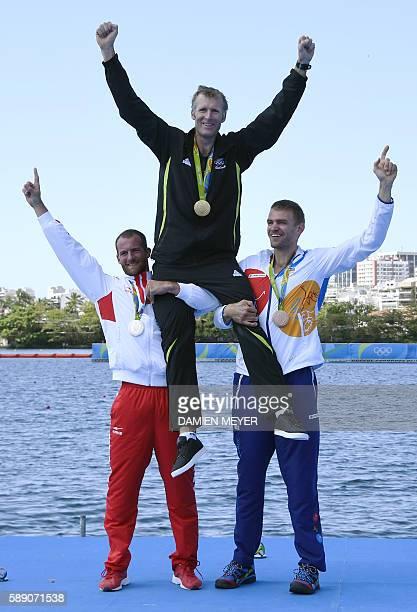 Gold medallist New Zealand's Mahe Drysdale is lifted by silver medallist Croatia's Damir Martin and bronze medallist Czech Republic's Ondrej Synek as...