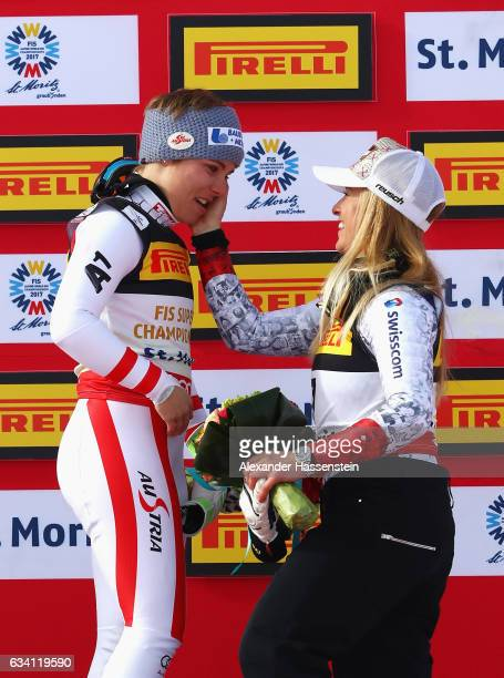 Gold medallist Nicole Schmidhofer of Austria is consoled by bronze medallist Lara Gut of Switzerland during the flower ceremony for the Women's Super...