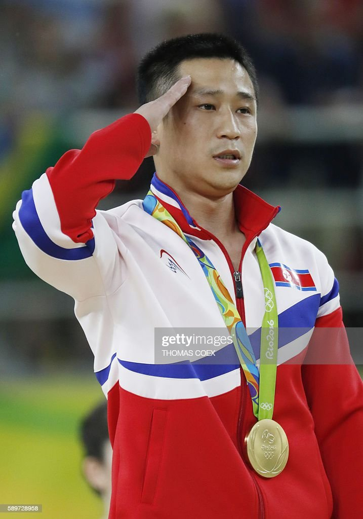 TOPSHOT Gold medallist North Korea's Ri Se Gwang salutes as he listens to his national anthem during the podium of the men's vault event final of the...
