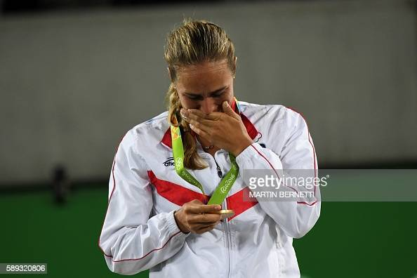 TOPSHOT Gold medallist Puerto Rico's Monica Puig reacts during the podium ceremony of the women's singles tennis event at the Olympic Tennis Centre...