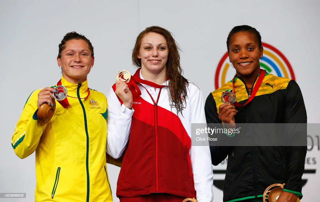 Gold medallist Sophie Taylor of England poses with silver medallist <a gi-track='captionPersonalityLinkClicked' href=/galleries/search?phrase=Lorna+Tonks&family=editorial&specificpeople=9060731 ng-click='$event.stopPropagation()'>Lorna Tonks</a> of Australia and bronze medallist <a gi-track='captionPersonalityLinkClicked' href=/galleries/search?phrase=Alia+Atkinson&family=editorial&specificpeople=881789 ng-click='$event.stopPropagation()'>Alia Atkinson</a> of Jamaica during the medal ceremony for the Women's 100m Breaststroke Final at Tollcross International Swimming Centre during day five of the Glasgow 2014 Commonwealth Games on July 28, 2014 in Glasgow, Scotland.