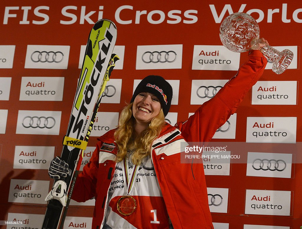 Gold medallist Swiss snowboarder Fanny Smith celebrates with her trophy on the podium of the Ladies' Skicross World Cup standings during the World Cup Super finals Snowboard and FreeStyle at Sierra Nevada ski resort near Granada on March 24, 2013. The Ski Cross race was cancelled today due to bad weather.