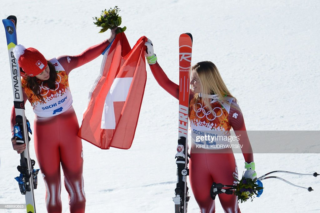 Gold medallist Switzerland's Dominique Gisin (L) and Switzerland's Lara Gut pose with the Swiss flag on the podium at the Women's Alpine Skiing Downhill Flower Ceremony at the Rosa Khutor Alpine Center during the Sochi Winter Olympics on February 12, 2014.