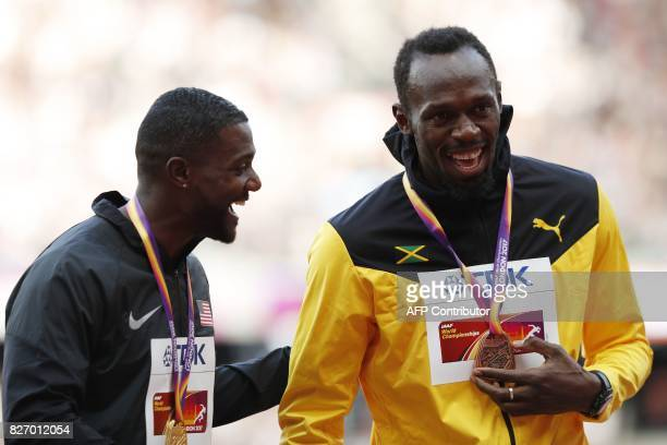 Gold medallist US athlete Justin Gatlin and bronze medallist Jamaica's Usain Bolt share a joke on the podium during the victory ceremony for the...