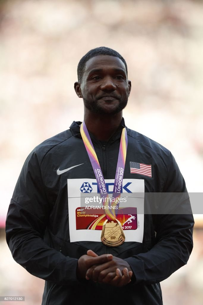 Gold medallist US athlete Justin Gatlin poses on the podium during the victory ceremony for the men's 100m athletics event at the 2017 IAAF World Championships at the London Stadium in London on August 6, 2017. / AFP PHOTO / Adrian DENNIS