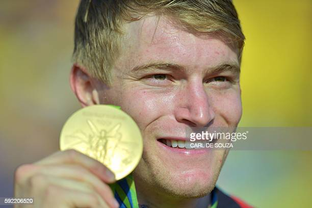 Gold medallist US Connor Fields celebrates on the podium of the men's BMX cycling event of the Rio 2016 Olympic Games at the Olympic BMX Centre in...