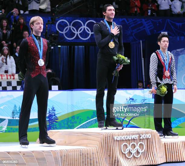 Gold medallist US Evan Lysacek poses on the podium flanked by silver medallist Russia's Evgeny Plushenko and bronze medallist Japan's Daisuke...
