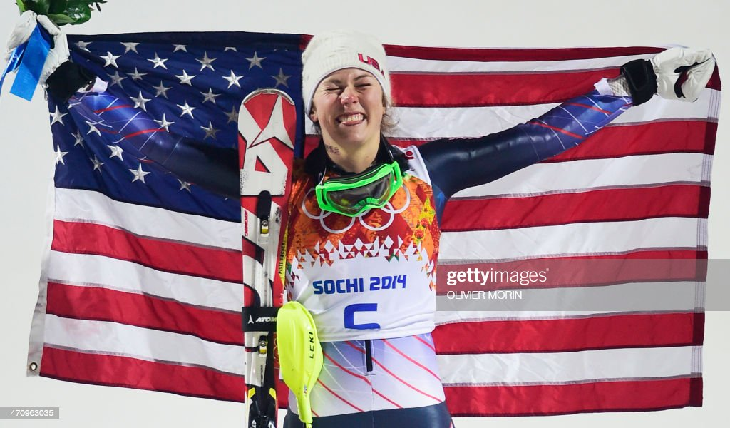 Gold medallist US skier Mikaela Shiffrin poses with the stars and stripes flag during the Women's Alpine Skiing Slalom Flower Ceremony at the Rosa Khutor Alpine Center during the Sochi Winter Olympics on February 21, 2014. AFP PHOTO / OLIVIER MORIN