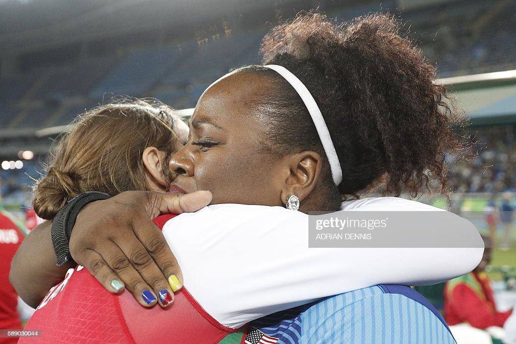 Gold medallist USA's Michelle Carter (R) is congratulated after winning the Women's Shot Put Final during the athletics event at the Rio 2016 Olympic Games at the Olympic Stadium in Rio de Janeiro on August 12, 2016. / AFP / Adrian DENNIS