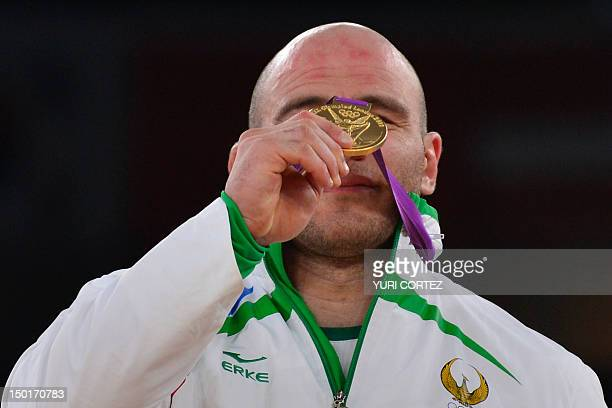 Gold medallist Uzbekistan's Artur Taymazov poses on the podium of the Men's 120kg on August 11 2012 during the wrestling event of the London 2012...