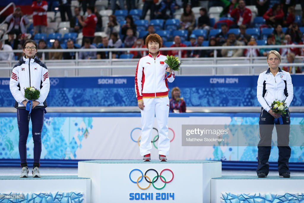 Gold medallist Yang Zhou (C) of China stands on the podium during the flower ceremony with silver medallist Suk Hee Shim (L) of South Korea and bronze medallist <a gi-track='captionPersonalityLinkClicked' href=/galleries/search?phrase=Arianna+Fontana&family=editorial&specificpeople=4680451 ng-click='$event.stopPropagation()'>Arianna Fontana</a> of Italy after the Ladies' 1500 m Final Short Track Speed Skating on day 8 of the Sochi 2014 Winter Olympics at the Iceberg Skating Palace on February 15, 2014 in Sochi, Russia.