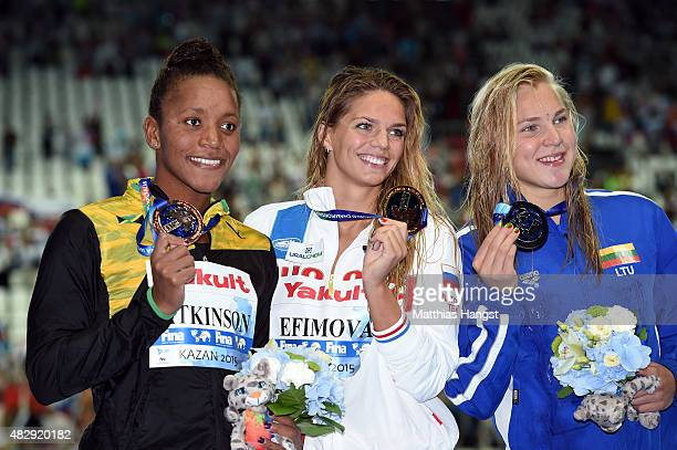 Gold medallist Yuliya Efimova of Russia poses with silver medallist Ruta Meilutyte of Lithuania and bronze medallist Alia Atkinson of Jamaica during...