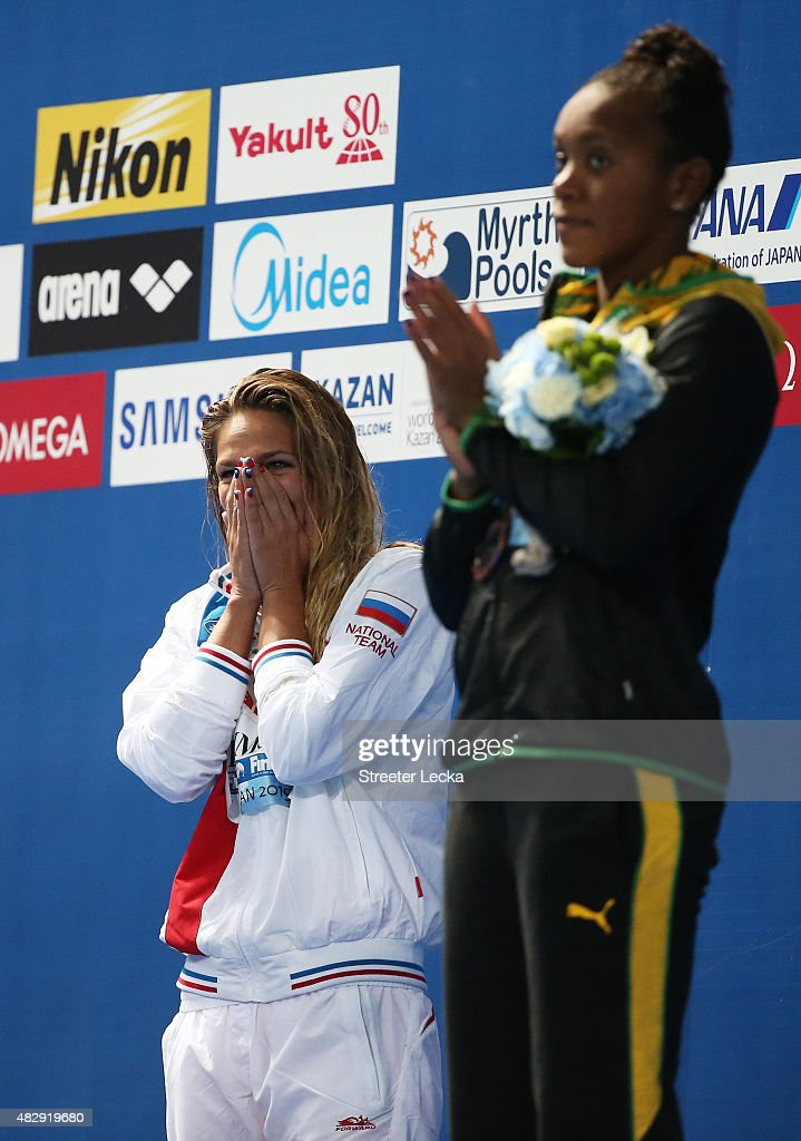 Gold medallist Yuliya Efimova of Russia reacts with bronze medallist Alia Atkinson of Jamaica during the medal ceremony for the Women's 100m Breaststroke Final on day eleven of the 16th FINA World Championships at the Kazan Arena on August 4, 2015 in Kazan, Russia.