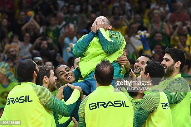 TOPSHOT Gold medallists Brazil toss up Brazil's Sergio Dutra Dos Santos after winning the men's Gold Medal volleyball match against Italy at the...