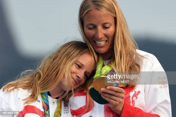 Gold medallists Britain's Hannah Mills and Saskia Clark celebrate on the podium of the 470 Women medal race at Marina da Gloria during the Rio 2016...
