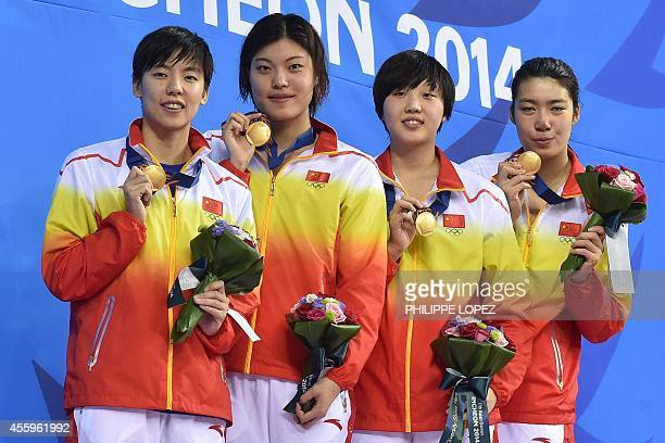 Gold medallists China's Guo Junjun Tang Yi Cao Yue and Shen Duo pose with their medals on the podium during the victory ceremony for the women's 4 x...