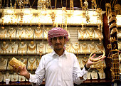 A gold merchant poses with his jewellery at the Dubai Gold Souk on September 25 2014 in Dubai United Arab Emirates