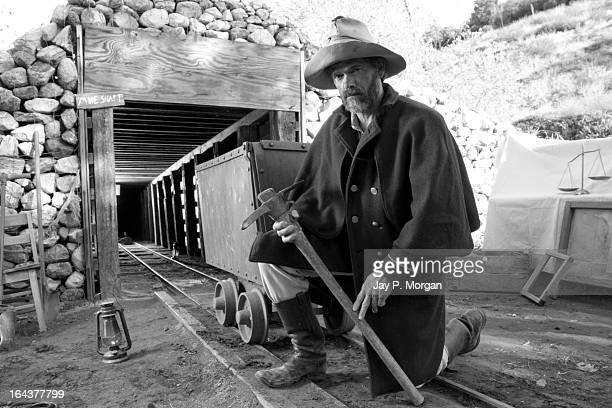 Gold miner in front of a mine shaft