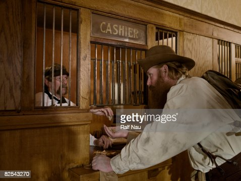 Gold miner selling gold to teller at bank : Photo