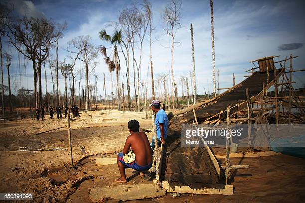 Gold miners watch National Police officers search for illegal mining operations in a deforested section of the Amazon lowlands on November 17 2013 in...