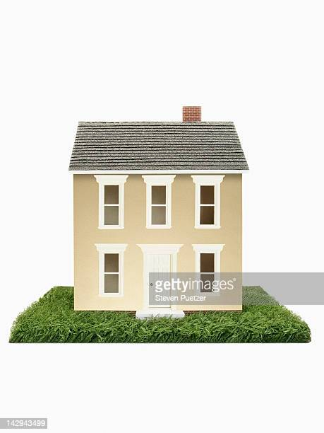 Gold model house on green grass
