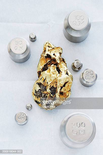 Gold nugget and scale weights, overhead view, close-up