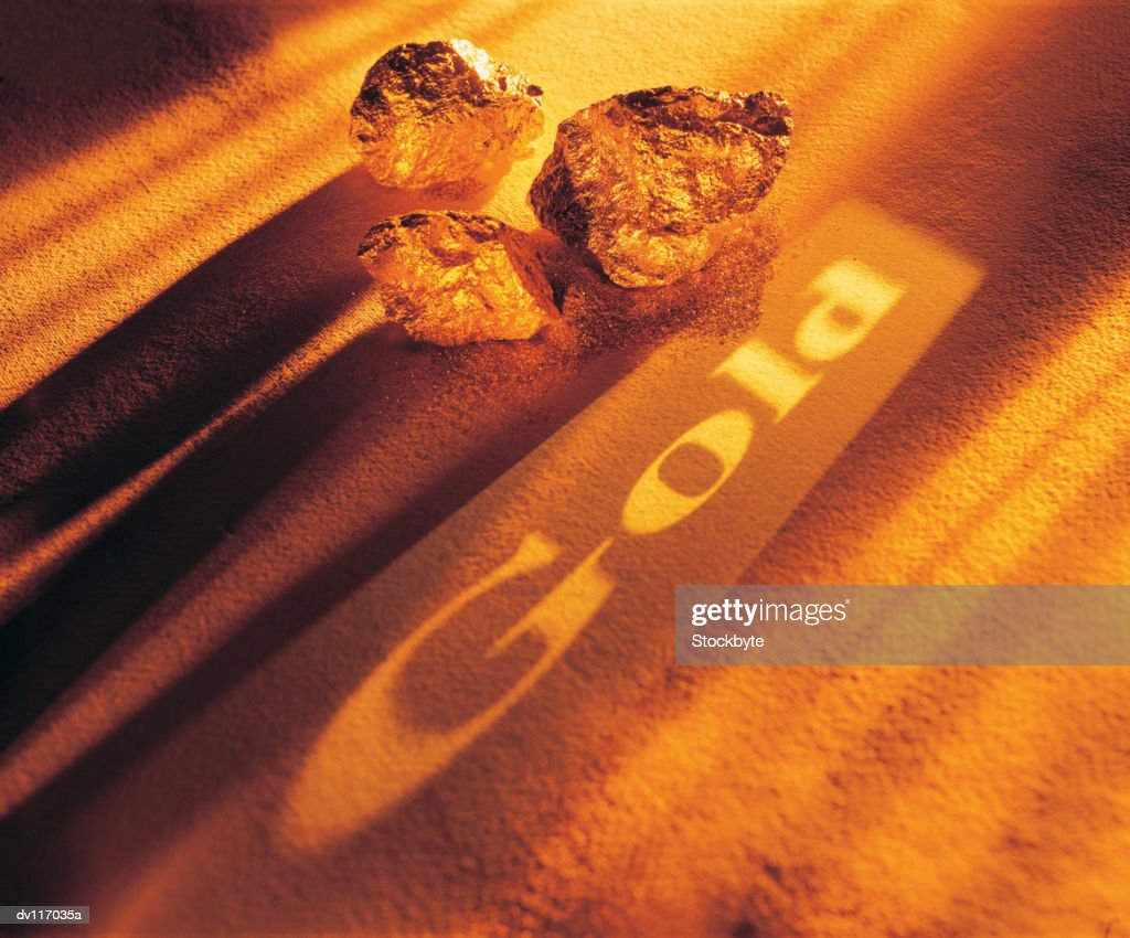 Gold nuggets beside word Gold projected onto gold dust : Stock Photo