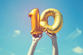 A gold foil number 10 balloon is held high in the air by caucasian male hand.  The image has been taken outdoors on a bright sunny day, the sky is blue with some clouds. A vintage style effects has be