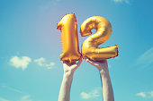 A gold foil number 12 balloon is held high in the air by caucasian male hand.  The image has been taken outdoors on a bright sunny day, the sky is blue with some clouds. A vintage style effects has be